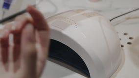 En ung flicka torkar spikar polermedel under en ultraviolett lampa i manikyrsalongen arkivfilmer
