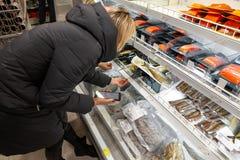 En ung flickablondin i ett långt omslag väljer matstundshopping arkivbilder