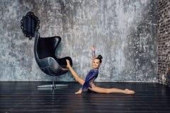 En ung flickagymnast i en blå dräkt gör sträckning av övning nära stolen mot den gråa väggen och leendena arkivbilder