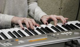 En ung flickapianist spelar det elektroniska pianot med hennes favorit- musik Kvinnliga behagfulla händer trycker på tangenterna  royaltyfri foto
