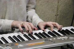 En ung flickapianist spelar det elektroniska pianot med hennes favorit- musik Kvinnliga behagfulla händer trycker på tangenterna  royaltyfri bild