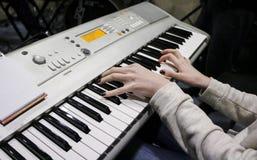 En ung flickapianist spelar det elektroniska pianot med hennes favorit- musik Kvinnliga behagfulla händer trycker på tangenterna  arkivfoton