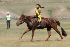En ung flickaridning under hästkapplöpningen Royaltyfri Foto