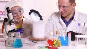 En ung forskare för kemigrupper för en skolflicka lager videofilmer
