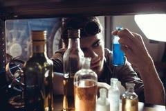 En ung forskarekemist väljer flaskor för experimentet Royaltyfri Foto