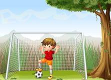 En ung fotbollsspelare nära det stora trädet Royaltyfria Bilder