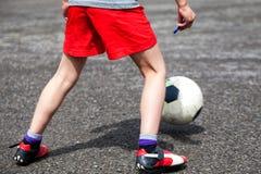 En ung fotbollsspelare som spelar bollen arkivbilder