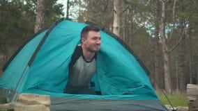 En ung grabb öppnar låset av det blåa tältet från insidan i skogen, ser ut ur den och tycker om ögonblicket arkivfilmer