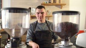 En ung grabb arbetar i en coffee shop, honom kastar en portafilter i hans hand lager videofilmer