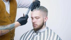En ung grabb får en frisyr med hårsax med en hårkam lager videofilmer