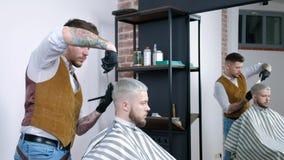 En ung grabb får en frisyr med hårsax med en hårkam arkivfilmer