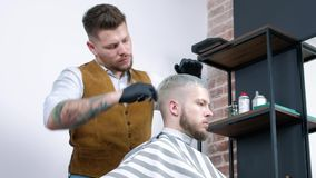 En ung grabb får en frisyr med hårsax med en hårkam stock video