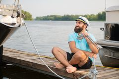 En ung grabb förtöjde hans yacht, medan sitta på pir arkivfoton
