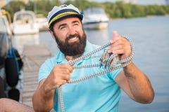En ung grabb förtöjde hans yacht, medan sitta på pir royaltyfri fotografi
