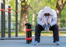 En ung grabb i ljus sportkl?der med en handduk p? hans huvud och en flaska av vatten i hans h?nder sitter p? idrottshallen i det  royaltyfri bild