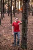 En ung grabb i en röd T-tröja i en pinjeskog royaltyfria foton
