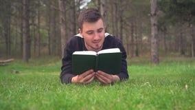 En ung grabb ligger p? det gr?na gr?set i skogen och l?ser en bok Vila avkoppling, n?je lager videofilmer