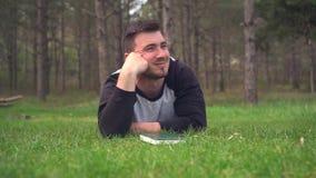 En ung grabb ligger p? det gr?na gr?set i skogen och l?ser en bok Vila avkoppling, n?je arkivfilmer