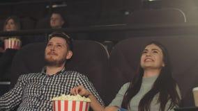 En ung grabb med en flickvän håller ögonen på en film på bion och äter popcorn stock video