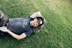 En ung grabb med en ryggsäck ligger på gräset och lyssnar till musik arkivfoton