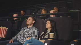 En ung grabb med en vän som håller ögonen på en film i en filmbiograf och skrattar på vad de såg på skärmen lager videofilmer