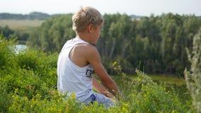 En ung grabb sitter på bankerna av floden Härlig sommarliggande Royaltyfri Bild
