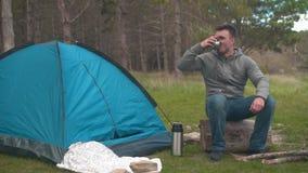 En ung grabb sitter på en stor journal nära ett blått tält i skogen och dricker te från en termos stock video
