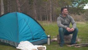 En ung grabb sitter på en stor journal nära ett blått tält i skogen och vilar stock video