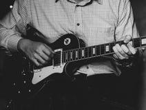 En ung grabb som spelar deppighet på en elektrisk gitarr Närbild arkivbilder
