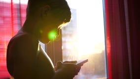 En ung grabb står nära ett fönster med en telefon i hans händer Solnedgångtid, passerar strålarna för sol` s in i rummet till och stock video
