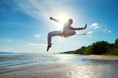 En ung grabb utbildar capoeira på stranden arkivfoto
