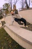 En ung grabb utför ett hopp till och med den konkreta balustraden royaltyfri fotografi