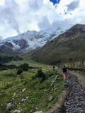 En ung grupp av internationella fotvandrare som ledas av deras lokala Incahandbok, navigerar de Anderna bergen på den Salkantay s arkivfoto
