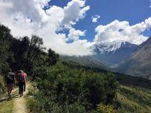 En ung grupp av internationella fotvandrare som ledas av deras lokala Incahandbok, navigerar de Anderna bergen på den Salkantay s royaltyfri bild