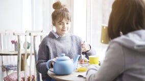 En ung gullig blyg kvinna som äter sallad i ett kafé arkivfoto