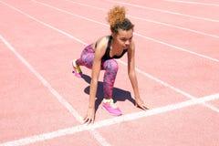 En ung härlig afrikansk amerikanflicka i en sportig svart T-tröja och rosa gymnastikskor förbereder sig att springa på den starta royaltyfri fotografi