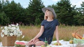 En ung härlig blond kvinna i en hatt och en klänning dricker lemonad från kan, medan sitta på en pläd på gräsplanen arkivfilmer
