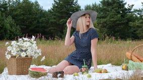 En ung härlig blond kvinna i en hatt och en klänning dricker lemonad från kan, medan sitta på en pläd på gräsplanen stock video