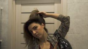 En ung härlig brunhårig kvinna som torkar hennes hår med en handfan efter dusch lager videofilmer