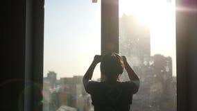 En ung härlig flicka att närma sig fönstret, öppnar fönsterramarna, solljus med linseffekten och värme luft tränger igenom stock video