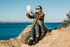 En ung härlig flicka gör selfie eller talar, genom att använda en minnestavla direktanslutet eller tar bilder av ett härligt land royaltyfri fotografi