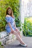 En ung härlig flicka i blått klär i parkera grön vägg; nolla arkivbilder