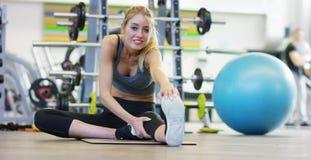 En ung härlig flicka i en idrottshall som lutar på hennes händer, skakar pressen och att göra långa moment som böjer henne knä Be Royaltyfria Bilder