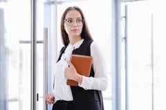 En ung härlig flicka i glasögon skriver in den glass kontorsdörren Royaltyfri Foto