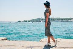 En ung härlig flicka i en hatt promenerar invallningen och tycker om en ferie i Turkiet och härliga sikter av Royaltyfria Foton