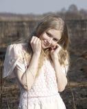 En ung härlig flicka i ljus kort-muff klänning lutar hennes kind på hennes näve Arkivbilder