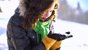 En ung härlig flicka i snö-täckt parkerar lutar över och tar snön med henne händer Hon stirrar på snöflingorna arkivfilmer