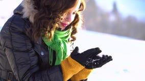 En ung härlig flicka i snö-täckt parkerar lutar över och tar snön med henne händer Hon stirrar på snöflingorna stock video