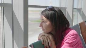 En ung härlig flicka sitter i det väntande rummet för flygplatsen stock video