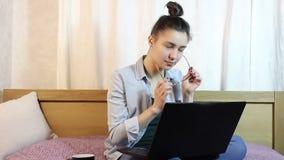 En ung härlig flicka som gnider hennes ögon från trötthet som arbetar på hennes bärbar dator arkivfilmer